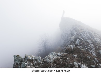 Man standing alone in the fog in mountains