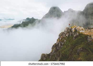 Man standing alone on mountain cliff edge foggy nature travel active healthy lifestyle outdoor adventure vacations in Norway