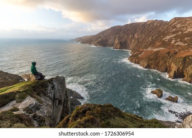 Man standing alone on the top of a cliff in Ireland