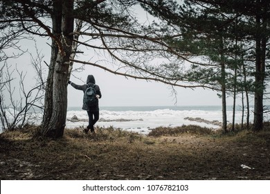 Man standing alone and watching frozen sea landscape, forest hike