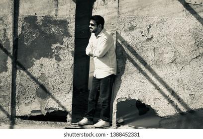 Man standing around an old broken metallic door