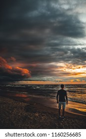 Man standing backwards and watching storm clouds by the sea coast.