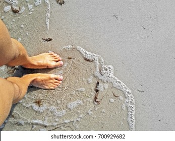 man standing with barefoot feet in water at beach
