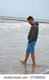 Man standing at the beach in the sand watching the empty sea with waves