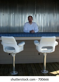 A man standing behind the bar in an outdoor cafe.