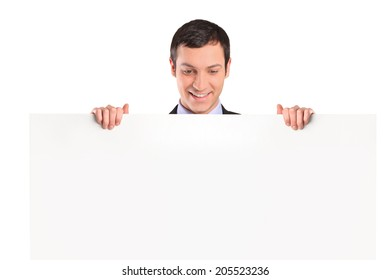 Man standing behind a blank billboard isolated on white background