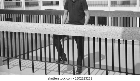 Man standing behind a protection grill of a building