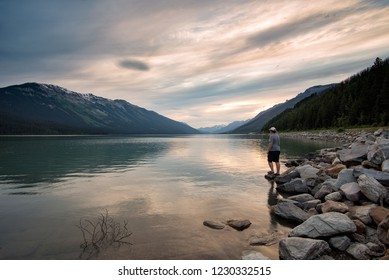Man standing beside a lake with a beautiful reflection.