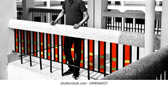 Man standing beside a metallic protection grill of a building