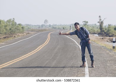 Man standing beside the road hitchhiking. Backpackers