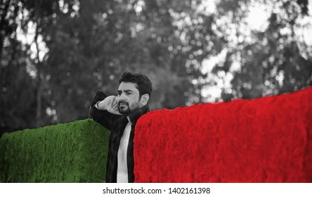 Man standing between a colourful clay made protection wall