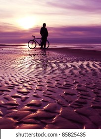 Man standing with bicycle on the beach