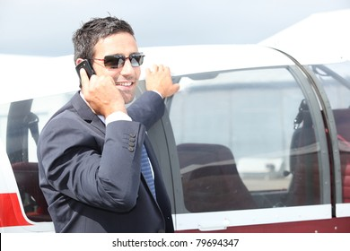 Man standing by the cockpit of a light aircraft talking on a cellphone