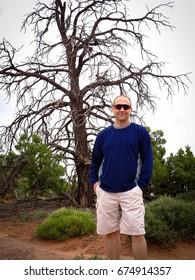 Man standing by dead tree