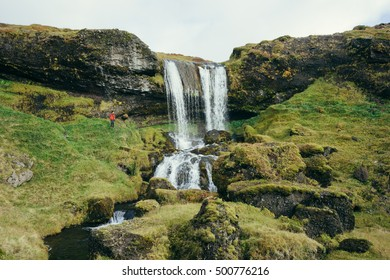 Man standing by idyllic waterfall in Iceland landscape with lush green grass