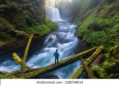 Man standing by a Koosah Falls, also known as Middle Falls, is second of the three major waterfalls of the McKenzie River, in the heart of the Willamette National Forest, in the U.S. state of Oregon.