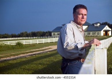 A man standing by a long white wooden fence bathed in the light of late afternoon sun.