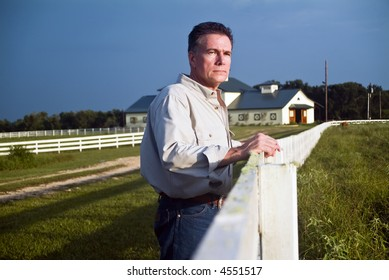 A man standing by a long white wooden fence looking out into the pasture.