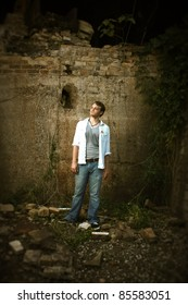A man standing by an old wall