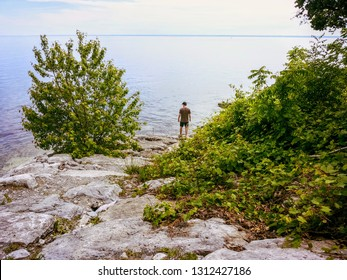 A man standing by the shore of Lake Ontario in Oakville, Ontari, Canada, staring out at the vast waters of the great lake deep in thought.