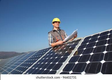 Man standing by solar panels with construction plan