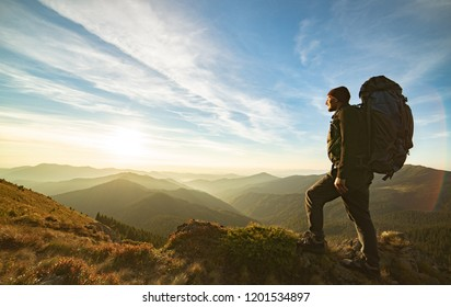 The man standing with a camping backpack on the rock with a picturesque sunrise