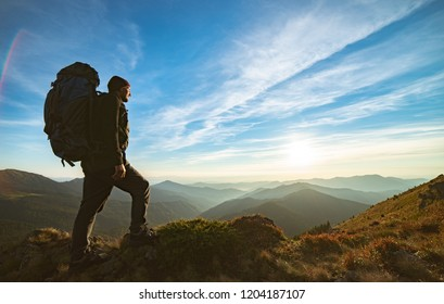 The man standing with a camping backpack on the rock with a picturesque sunset