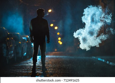 The man standing in the cloud of smoke. Evening night time. Telephoto lens shot