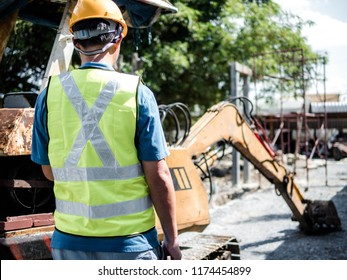 Man standing in a construction site with digger loading trucks