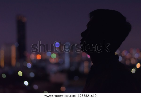 A man standing in darkness alone looking to somewhere with colorful city bokeh lights as background. Stay home, depression and loneliness concept.