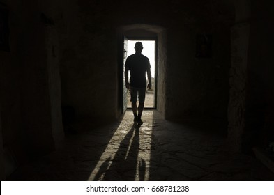 Man standing in door way. Light and shadow on casting on floor. Mystical abstract photo.