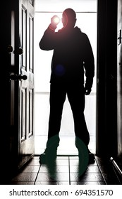 Man standing at doorway threshold, in silhouette with flashlight creating glare