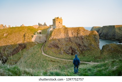 Man standing at the edge of a cliff. Enjoying the beautiful ocean scenery. Taken in Dunottar Castle at západu slunce on the East Coast of Scotland. Aberdeenshire, United Kingdom   - Shutterstock ID 1397752757