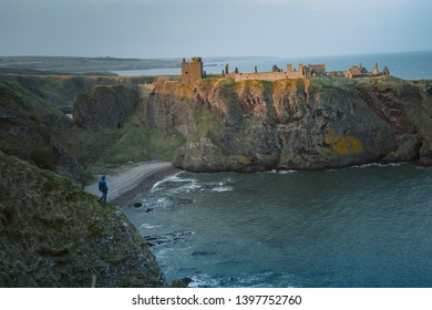 Man standing at the edge of a cliff. Enjoying the beautiful ocean scenery. Taken in Dunottar Castle at západu slunce on the East Coast of Scotland. Aberdeenshire, United Kingdom   - Shutterstock ID 1397752760