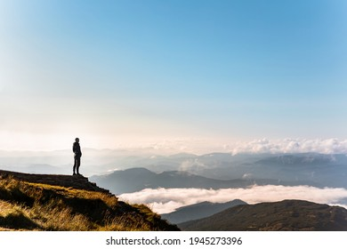 man standing at the edge of the cliff looking at mountains. clouds below