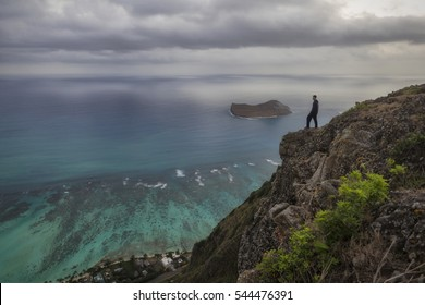 Man standing at the edge of a cliff looking out over the coast just before sunrise. Rabbit island is in the background. Oahu, Hawaii.