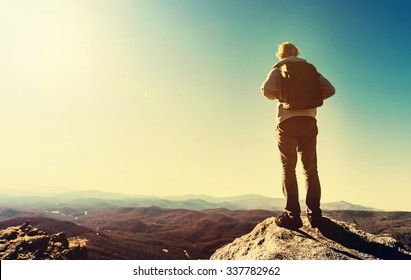 Man standing at the edge of a cliff overlooking the mountains below