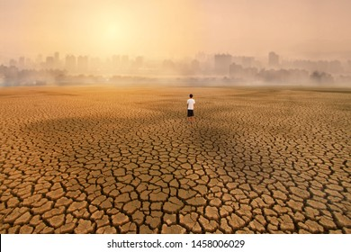 a man standing at empty land of dry cracked earth and looking to the big city with air polluted environment metaphor Climate change, Water crisis, Environment pollution of activity from urban concept.