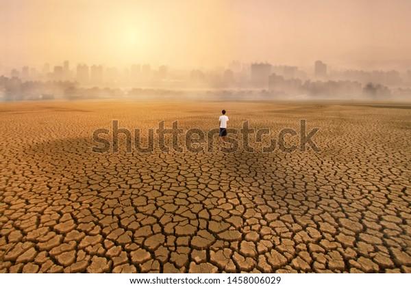 ein Mann, der auf einem leeren Land mit trockener, zerrissener Erde steht und in die Großstadt blickt, mit der Metapher Klimaveränderung, Wasserkrise, Umweltverschmutzung durch Aktivitäten aus dem städtischen Konzept.