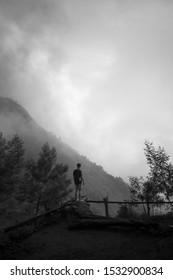 man standing enjoying scenery in black and white
