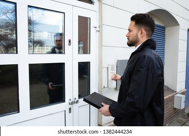 Man Standing At The Entrance Of The House Pressing The Door Bell