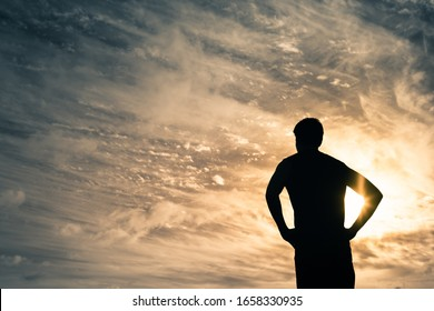 Man standing facing the sunset sky.