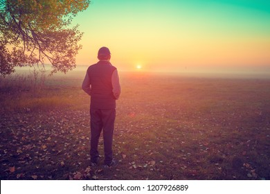 A man standing in the field in early morning and looking at sunrise