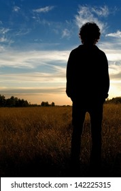 Man standing in field looking into distance