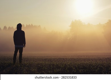 Man standing in the fog at sunrise
