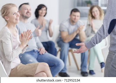 Man standing in front of applauding support group after making progress