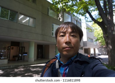 a man standing in front of architecture of hillside terrace at daikanyama in tokyo, japan