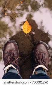 Man standing in front of autumn leaf in a puddle
