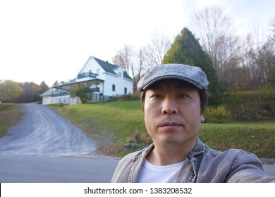 a man standing in front of beautiful house at marbleton town of dudswell on the townships trail of eastern townships in quebec, canada