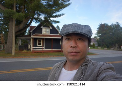 a man standing in front of beautiful house at bishopton town of dudswell on the townships trail of eastern townships in quebec, canada